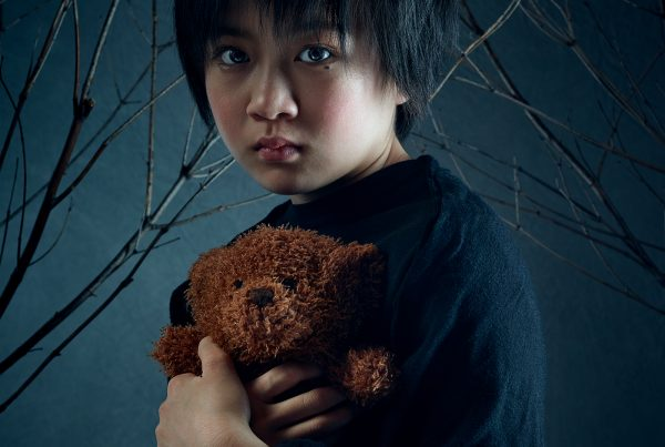 A sad-looking child holds a teddy bear under an arch of leadless branches representing a dark wood in this creative image for The Winter's Tale