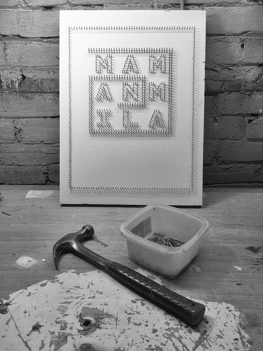 """Nails in a board spelling out """"Mammalian"""" beside a container of nails and a hammer"""